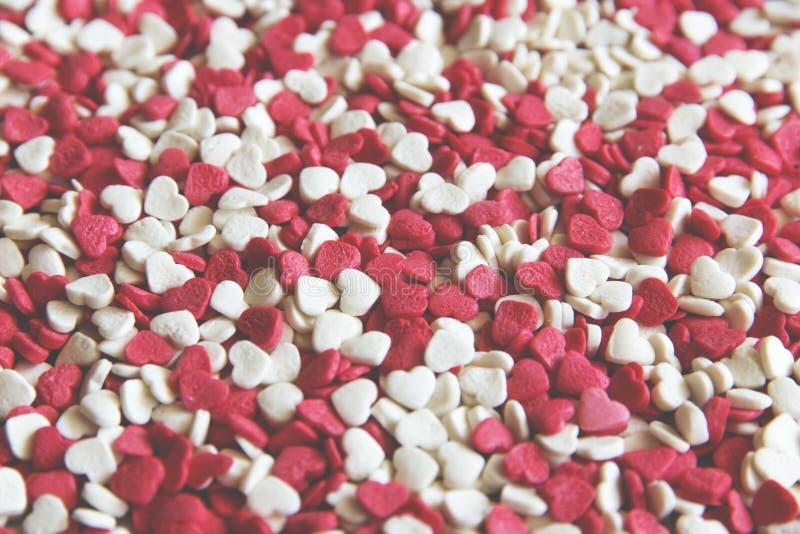 Fundo festivo elegante com as decorações do açúcar sob a forma do coração na superfície textured branco com espaço para o texto o imagem de stock