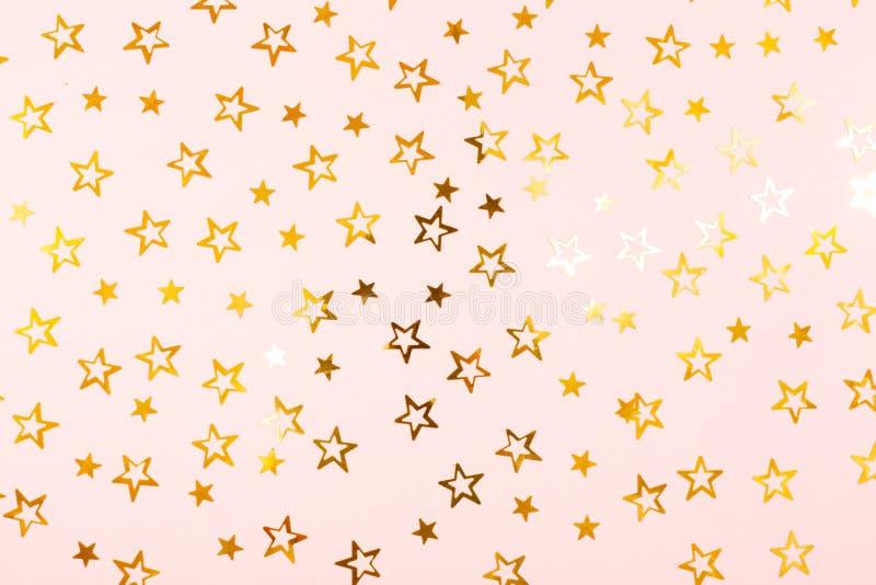 Fundo festivo Estrelas douradas dos confetes no papel cor-de-rosa foto de stock
