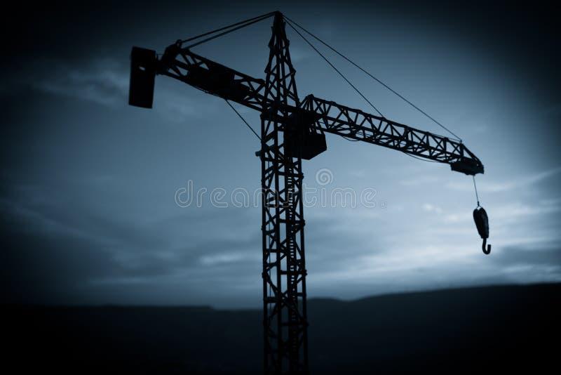 Fundo industrial abstrato com a silhueta do guindaste de constru??o sobre o c?u de surpresa do por do sol Guindaste de torre cont foto de stock royalty free