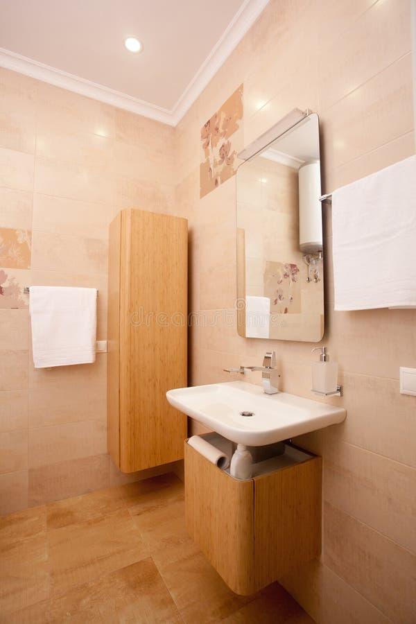 Fundo interior minimalistic vazio, banheiro do apartamento moderno, espelho e bacia em cores claras fotografia de stock royalty free