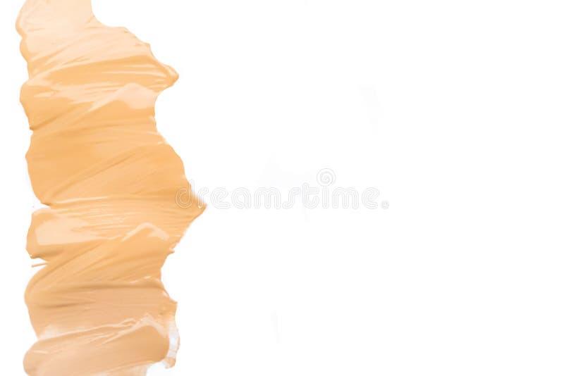 Fundo isolado creme do borrão da fundação da composição Base tonal corretiva da colagem da vista superior Tom de pele tonal macro fotos de stock royalty free