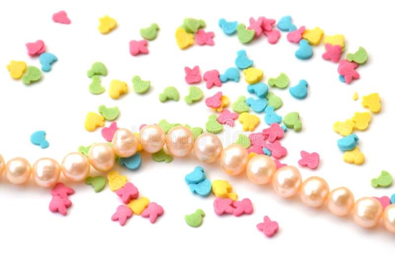 Fundo isolado de confeitos brilhantes que cobre no formulário dos animais e na corda de grânulos de pérolas do rosa de mar no bra foto de stock