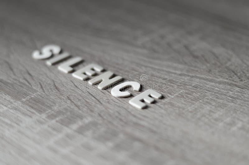 Fundo Letras na tabela de madeira ` Do silêncio do ` imagens de stock