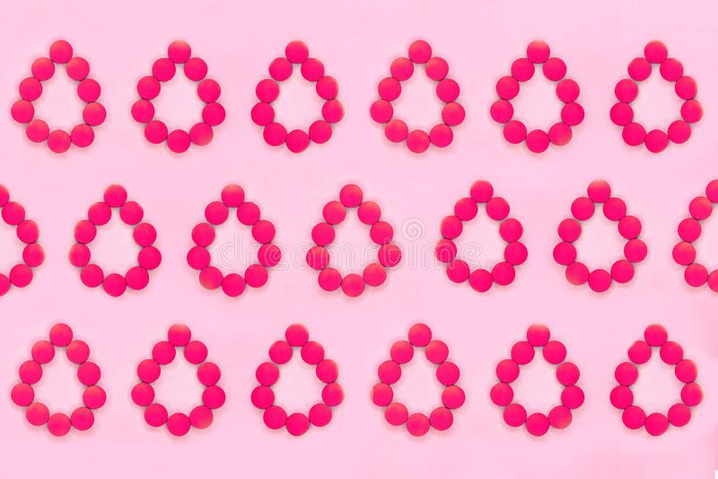 Fundo médico dos períodos das mulheres Comprimidos vermelhos sob a forma das gotas de sangue em um fundo cor-de-rosa fotos de stock