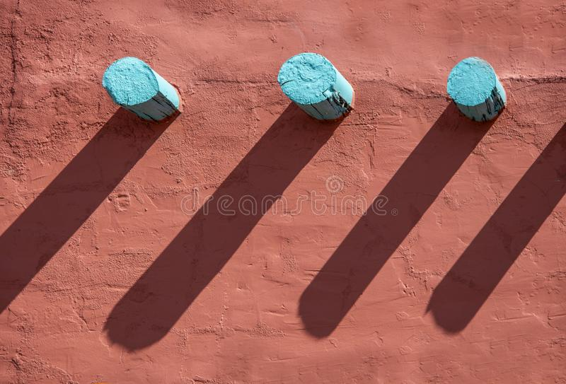 Fundo - mísulas de turquesa e suas sombras longas em uma parede alaranjada do estuque na construção do sudoeste do estilo imagens de stock royalty free