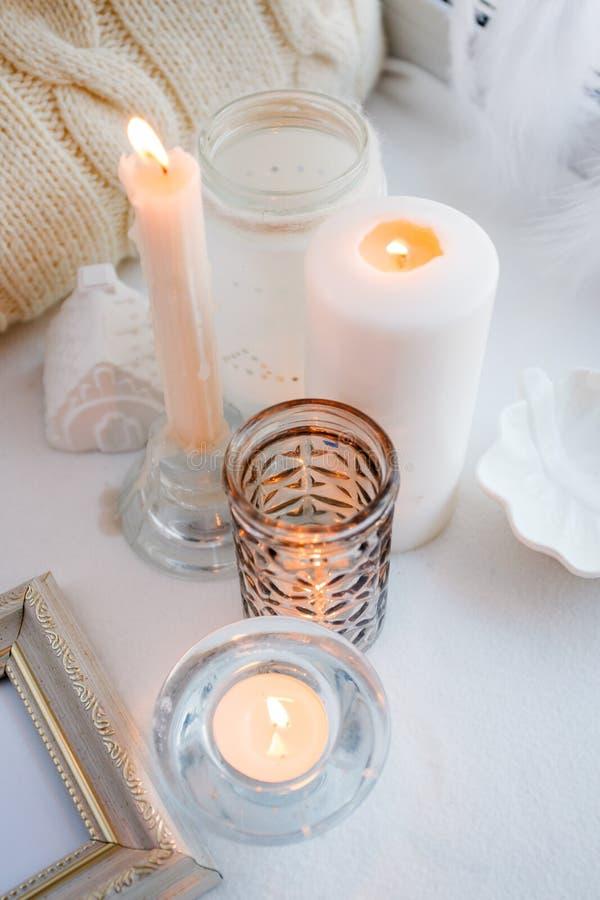 Fundo monocromático branco confortável da mola acolhedor e macia do inverno, descanso feito malha e velas na placa da soleira Fer imagem de stock