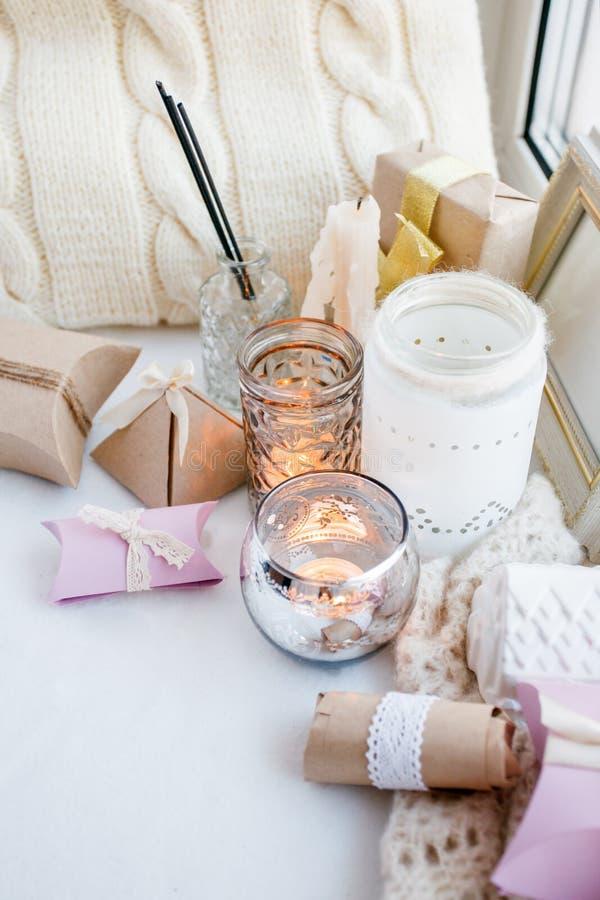 Fundo monocromático branco da mola confortável e macia do inverno, descanso feito malha e velas na placa da soleira Feriados do N foto de stock
