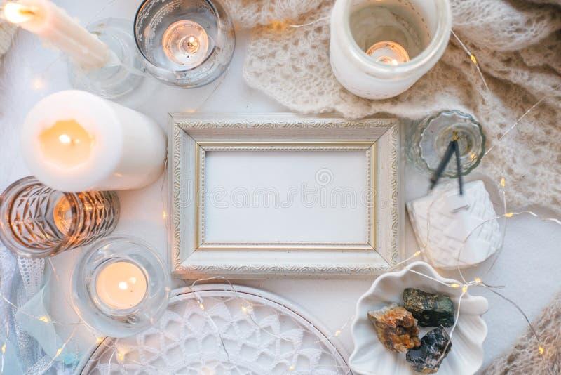 Fundo monocromático branco da mola confortável e macia do inverno, lenço feito malha, coletor ideal e velas no branco Feriados do foto de stock