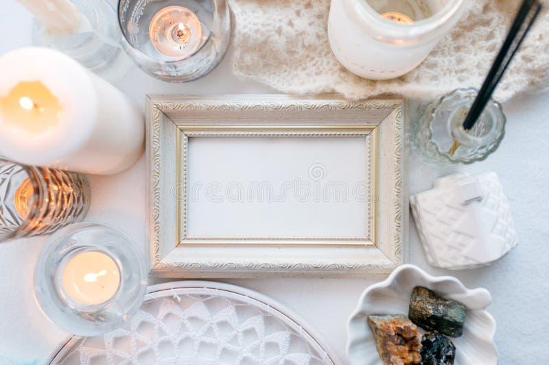 Fundo monocromático branco da mola confortável e macia do inverno, lenço feito malha, coletor ideal e velas no branco Feriados do imagens de stock