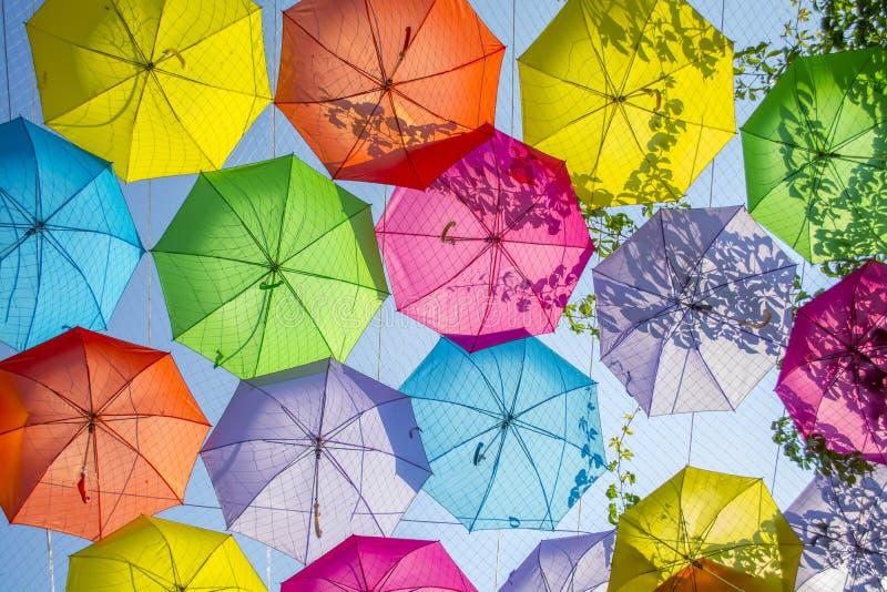 fundo Multi-colorido dos guarda-chuvas Guarda-chuvas coloridos que flutuam acima da rua Decoração da rua fotografia de stock royalty free