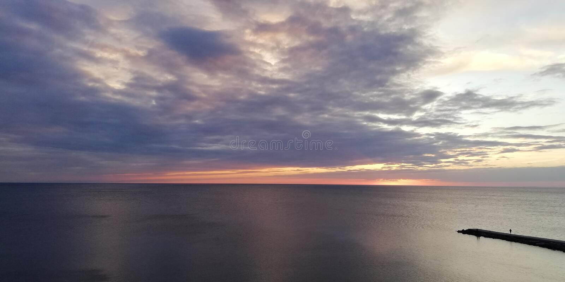 Fundo natural de perturbação pitoresco Seascape do por do sol Contraste do céu claro e de nuvens escuras Silhuetas dos povos em u fotos de stock