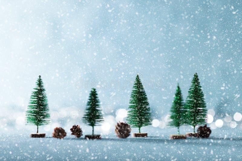 Fundo nevado mágico do país das maravilhas do inverno Árvores e cones sempre-verdes diminutos do pinho no fundo azul brilhante co foto de stock