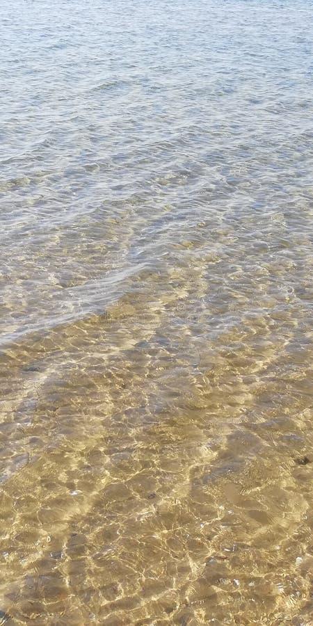 Fundo O brilho do sol na ?gua do mar A parte inferior do mar atrav?s das ondas em um dia ensolarado do ver?o imagens de stock royalty free