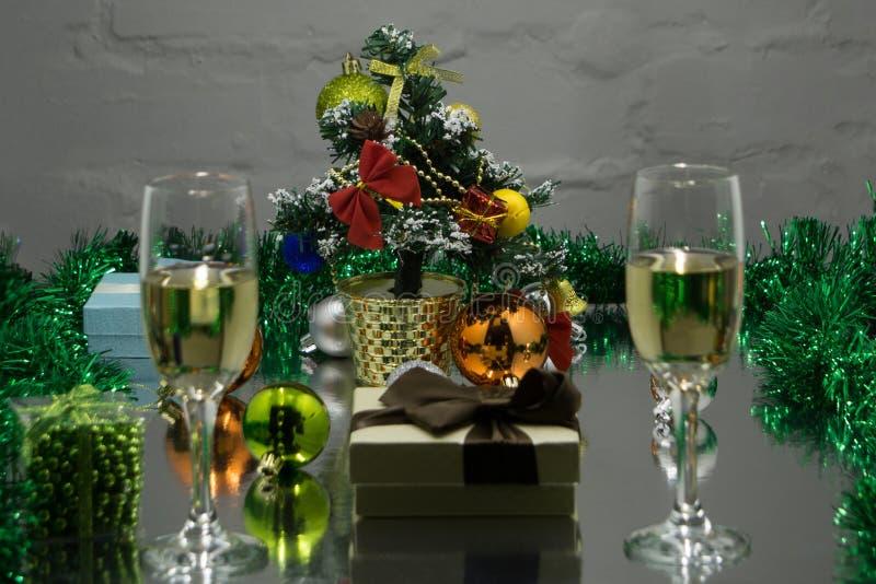 Fundo obscuro abstrato: Natal ou ano novo Champagne nos vidros com velas, o panettone e o presente com cetim vermelho curvam-se C fotografia de stock
