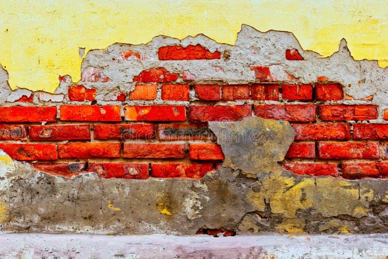 Fundo ou contexto do tijolo vermelho velho Decayed e emplastro amarelo na parede desigual exterior da casa com o gasto lavado suj fotos de stock royalty free