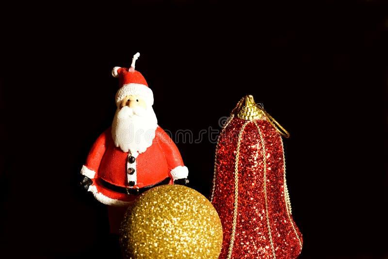 Fundo para o cartão do Natal Decorações do Natal, bola dourada e vela de Santa Claus fotografia de stock