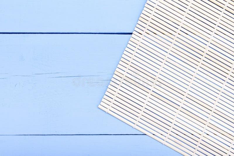 Fundo para o restaurante asiático Esteira de bambu na tabela de madeira azul Vista superior com espaço da cópia fotografia de stock royalty free