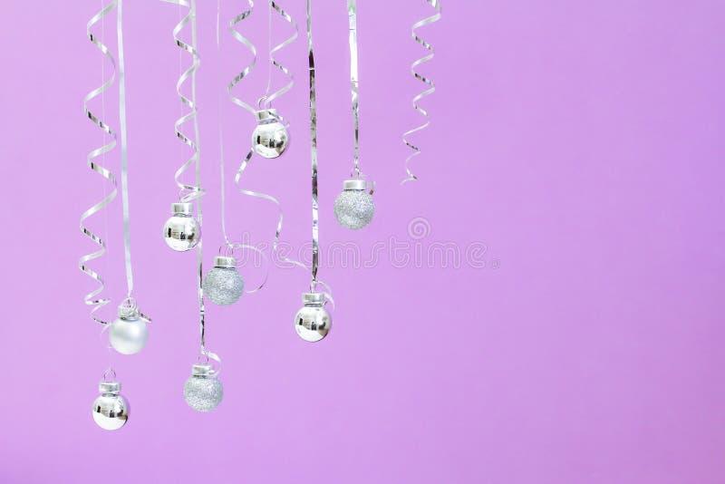 Fundo pastel na moda do Natal Ornamento de prata da bola que penduram no fundo ultravioleta Conceito mínimo do Natal imagem de stock