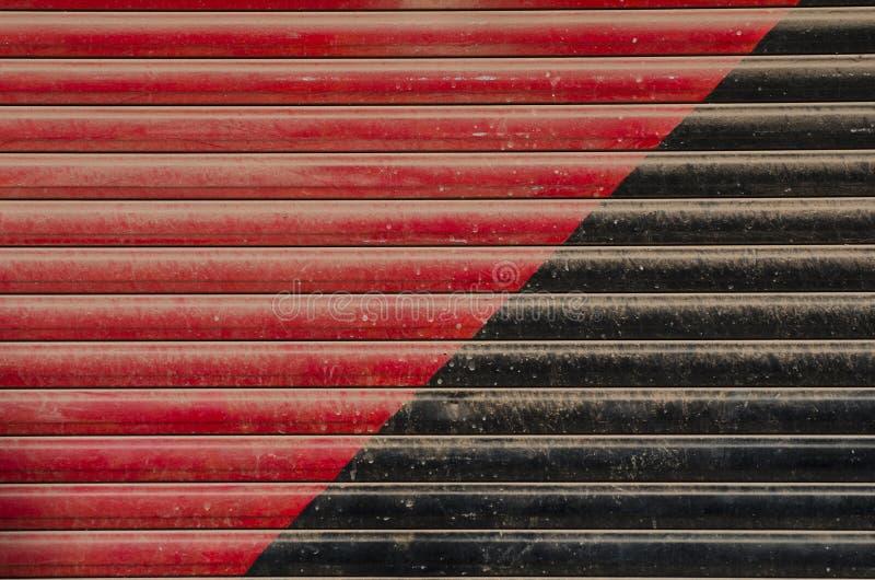 Fundo pintado vermelho e preto da porta do metal foto de stock