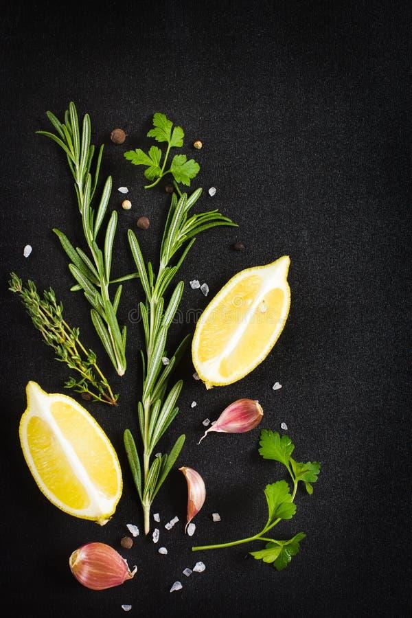 Fundo preto do alimento com as ervas e as especiarias aromáticas frescas, cópia foto de stock royalty free