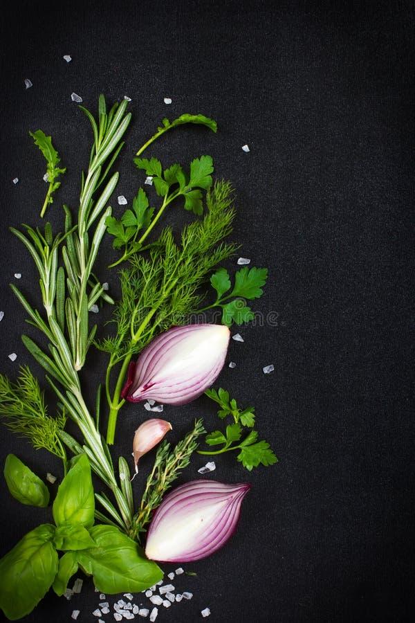 Fundo preto do alimento com as ervas e as especiarias aromáticas frescas, cópia fotografia de stock