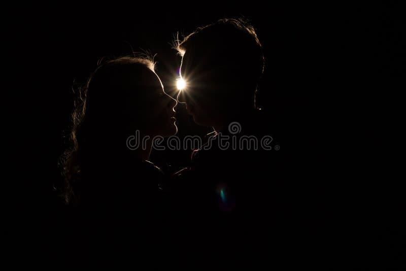Fundo preto, pares, cabeças, entre eles uma luz, um raio do beijo inacabado claro o começo de um beijo fotografia de stock