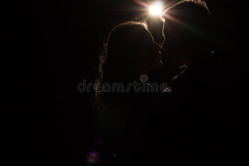 Fundo preto, pares, cabeças, entre eles uma luz, um raio do beijo inacabado claro o começo de um beijo imagens de stock royalty free