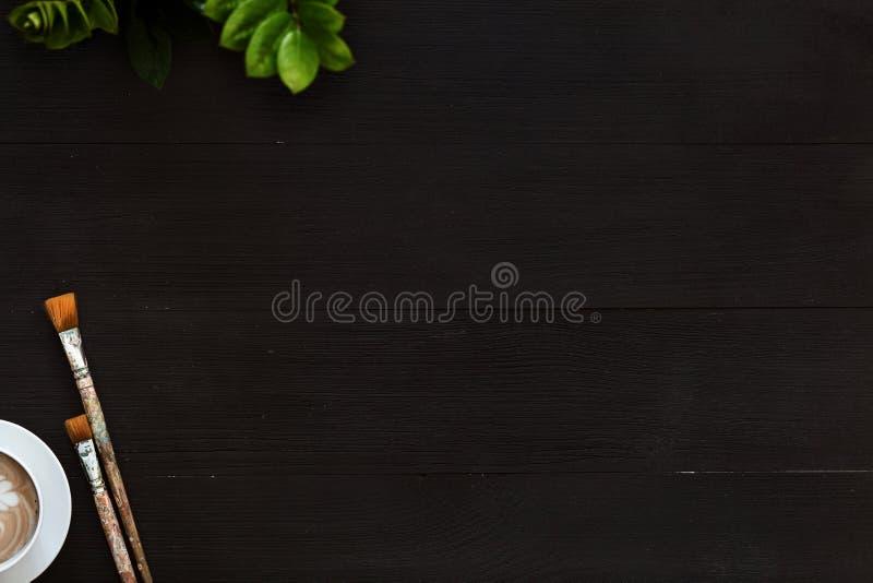 Fundo preto vazio de madeira da arte criativa com café e pincéis imagem de stock