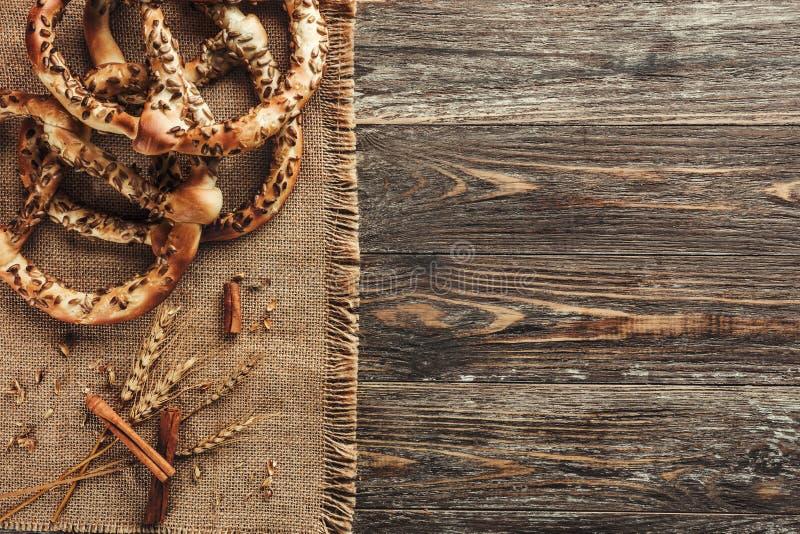 Fundo, pretzeis ou bretzels e varas de canela rústicos na tabela de madeira Conceito da pastelaria, vista superior imagem de stock royalty free
