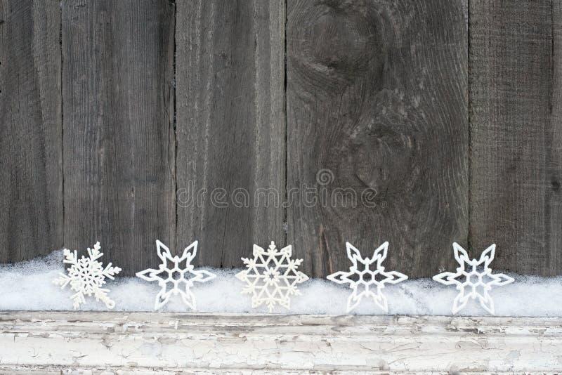 Fundo rústico do inverno com flocos de neve do brilho e neve na textura de madeira Fundo do cartão do Natal e do ano novo fotos de stock