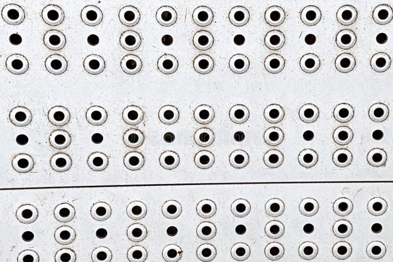 Fundo resistido brilhante da superfície de aço de prata metálica com fileira horizontal horizontal de muitos furos redondos foto de stock royalty free