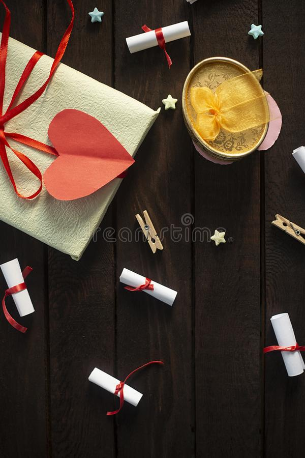 Fundo romântico colocado plano Caixa de presente com bloco rolado do presente do papel dos desejos na placa de madeira foto de stock