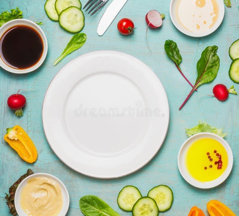 Fundo saudável do alimento com os ingredientes da salada com vário molho e a placa vazia, vista superior Faça dieta comer imagens de stock royalty free