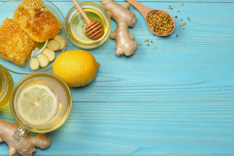 Fundo saudável mel, favo de mel, limão, chá, gengibre na tabela de madeira azul Vista superior com espaço da cópia fotos de stock royalty free
