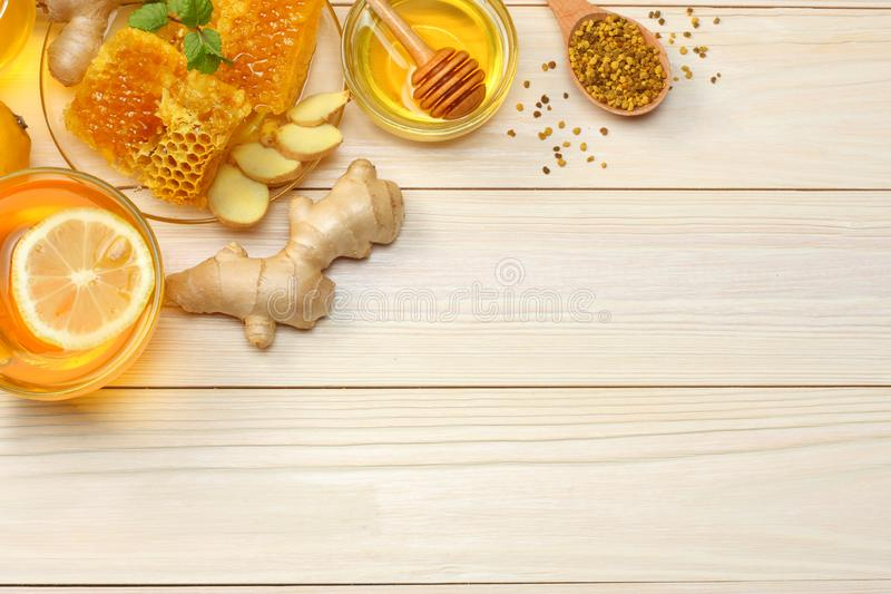 Fundo saudável mel, favo de mel, limão, chá, gengibre na tabela de madeira branca Vista superior com espaço da cópia fotografia de stock