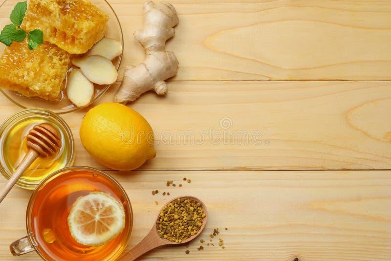 Fundo saudável mel, favo de mel, limão, chá, gengibre na tabela de madeira branca Vista superior com espaço da cópia imagem de stock royalty free