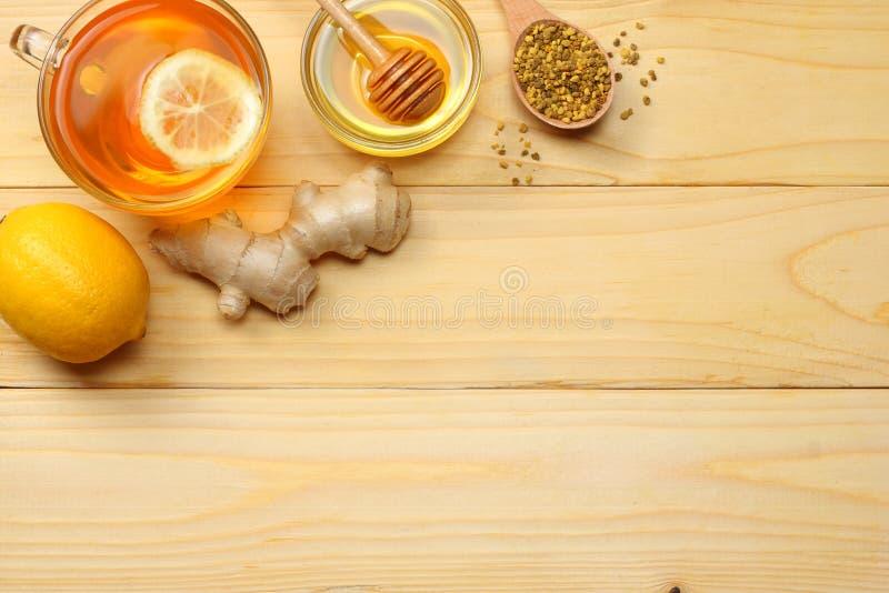 Fundo saudável mel, favo de mel, limão, chá, gengibre na tabela de madeira clara Vista superior com espaço da cópia foto de stock royalty free