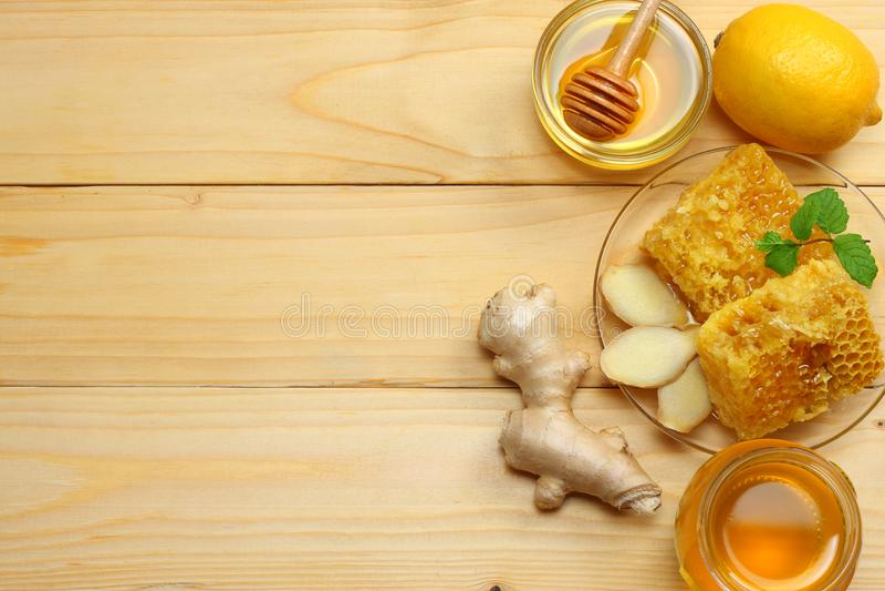 Fundo saudável mel, favo de mel, limão, chá, gengibre na tabela de madeira clara Vista superior com espaço da cópia fotografia de stock