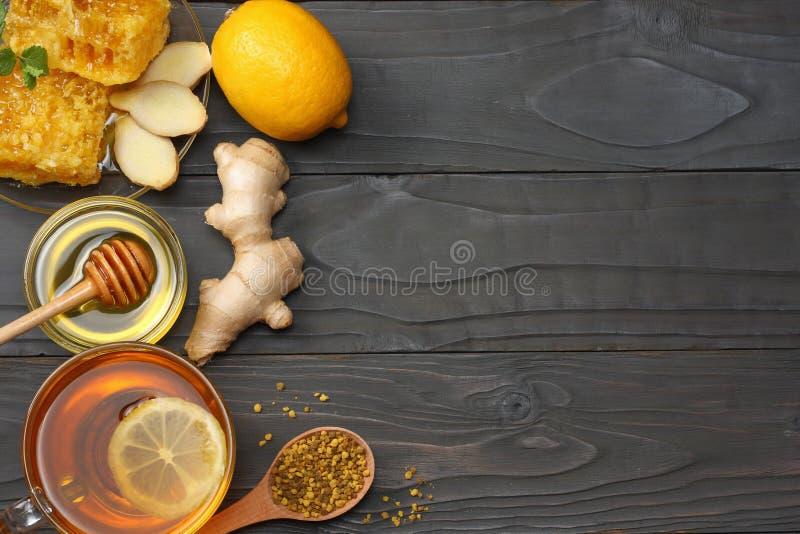 Fundo saudável mel, favo de mel, limão, chá, gengibre na tabela de madeira escura Vista superior com espaço da cópia fotografia de stock royalty free