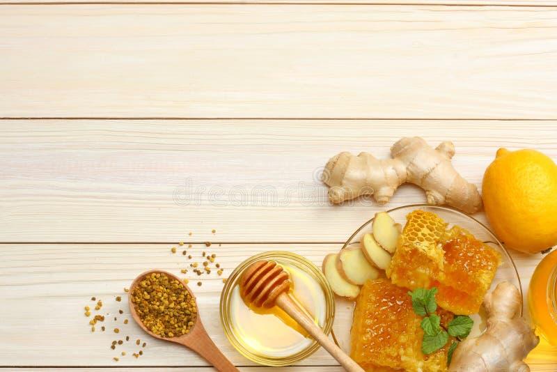 Fundo saudável mel, favo de mel, limão, gengibre na tabela de madeira branca Vista superior com espaço da cópia imagem de stock