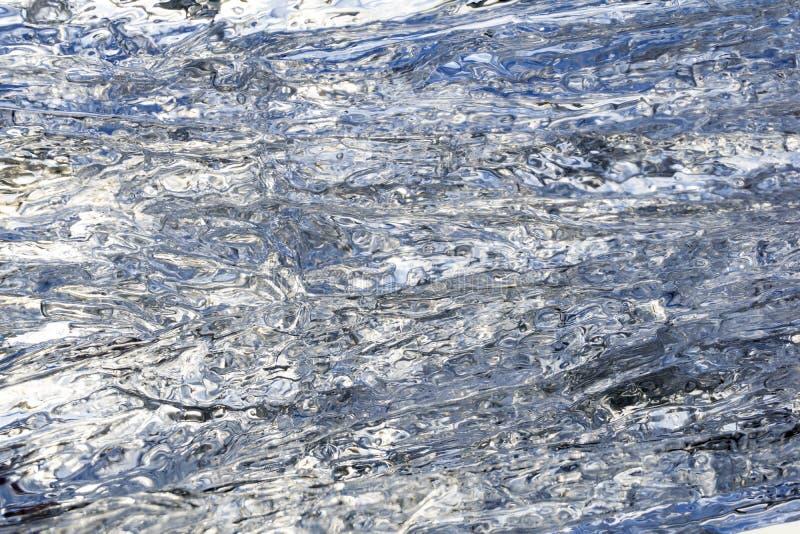 Fundo, textura - superfície ondulada do gelo de derretimento imagem de stock