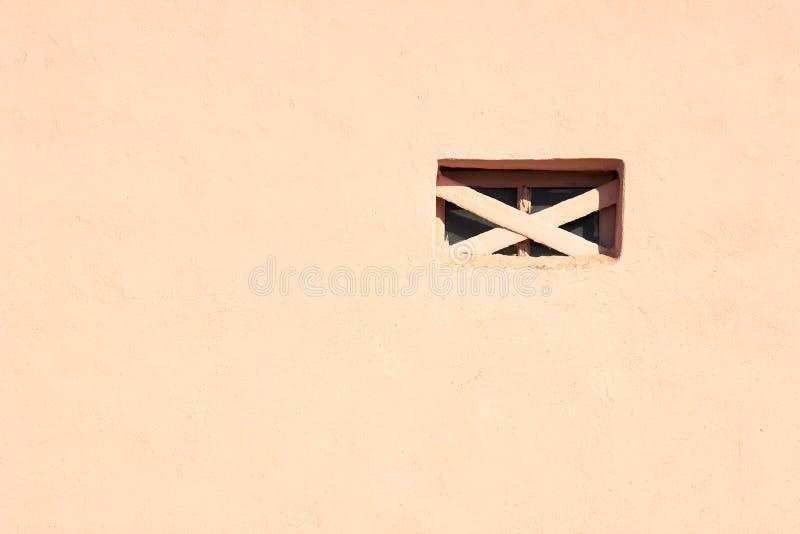 Fundo texturizado de parede de construção abstrato pintado com cor de coral vivo claro e abertura de janela com barra cruzada foto de stock royalty free