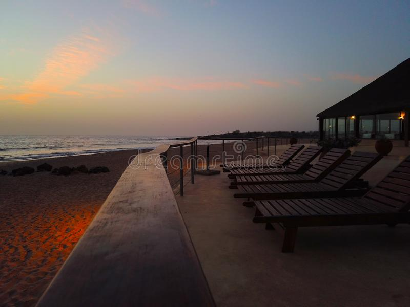 Fundo tropical com pares de cadeiras de plataforma no por do sol pelo mar É vista bonita do sol dourado do hotel imagem de stock royalty free