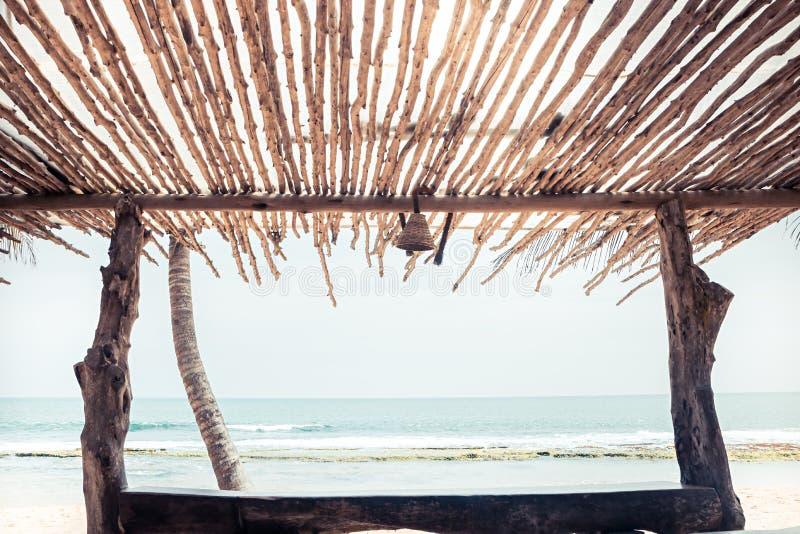 Fundo tropical do vintage da praia com abrigo do dossel da sombra da opinião do mar fotografia de stock