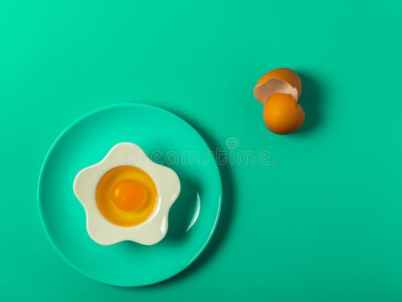 Fundo verde com ovo em uma bacia dada forma flor e em uma placa verde com escudos de ovo e os utensílios quebrados da cozinha imagem de stock royalty free