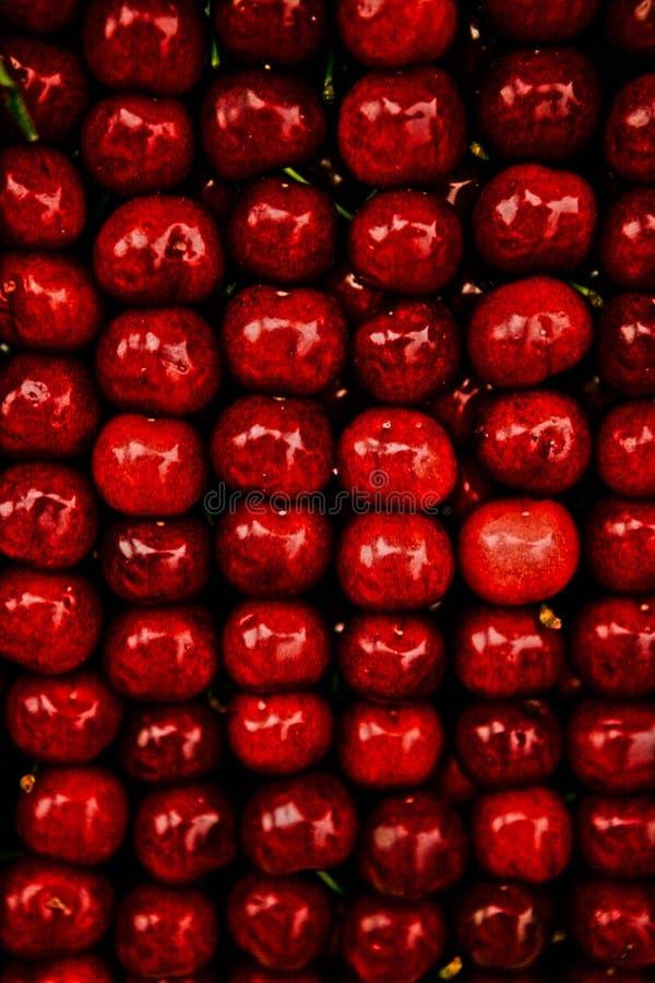 Fundo vermelho brilhante das cerejas doces suculentas ordenadamente dobradas fotos de stock