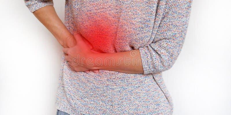 Fundo vermelho da área da dor Uma mulher que sofre da dor abdominal Problema de saúde Mulher que guarda as mãos em seu estômago imagens de stock royalty free