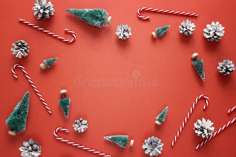 Fundo vermelho do Natal com abetos, bastões de doces e cones do pinho fotografia de stock