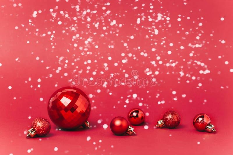 Fundo vermelho do Natal com bolas do Natal e neve que cai nelas foto de stock royalty free