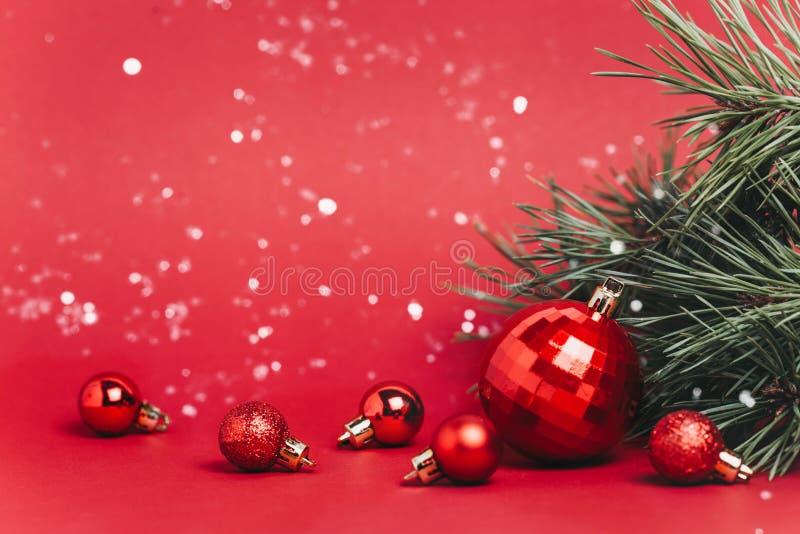Fundo vermelho do Natal com bolas do Natal e neve que cai nelas imagem de stock royalty free